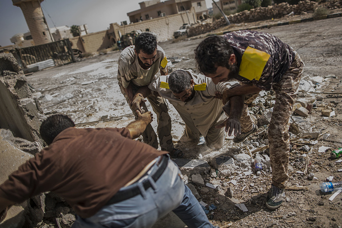 A fighter of the Libyan forces is helped by comrades after being shot by a sniper, in Sirte, Libya, October 2