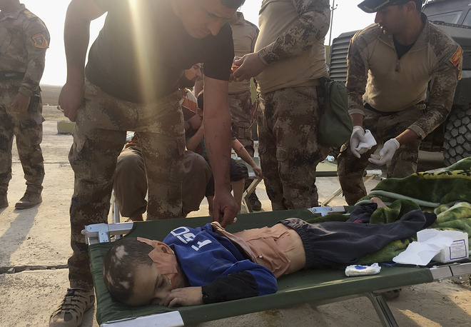 Soldiers give the first aid to a boy injured during the clashes between Iraq's elite counterterrorism forces and Islamic State militiants in the village of Tob Zawa