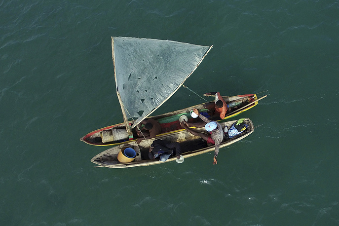Fishermen sail their wooden boats in the bay of Port-au-Prince, Haiti, November 23