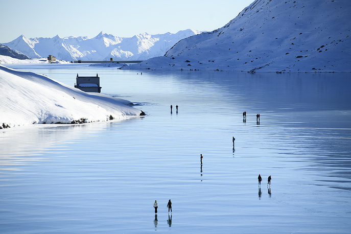People enjoy a sunny day on the 'black ice' of Lago Bianco lake on the Bernina pass in Grisons, Switzerland