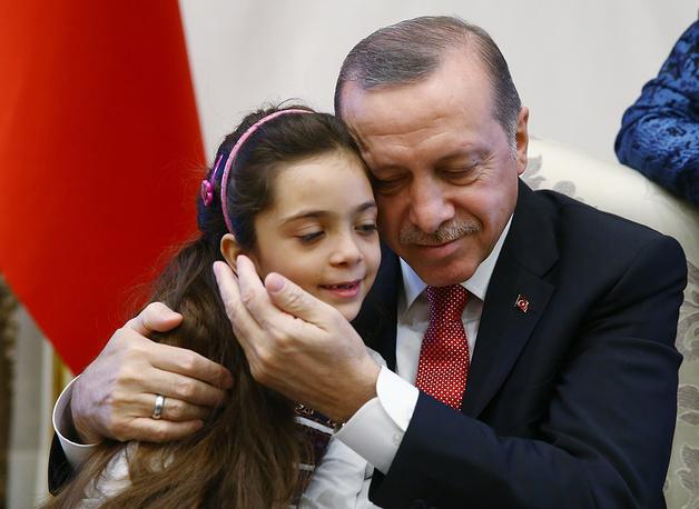 Turkey's President Recep Tayyip Erdogan embraces 7-year old Syrian girl Bana Al-Abed, who was evacuated from Aleppo, in Ankara, Turkey, December 21