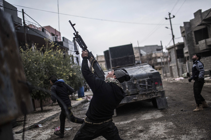 A member of the Iraqi Special Forces shoots his machine gun against an Islamic State militant drone in the al-Barid district in Mosul, Iraq, December 18