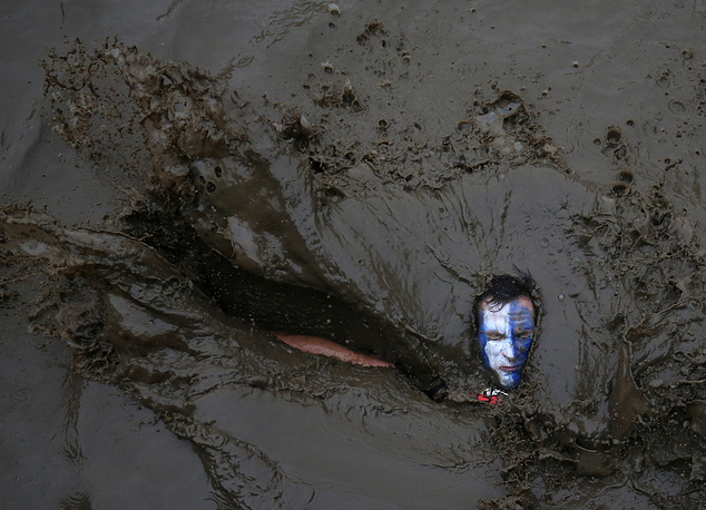 A competitor falls in mud during the Tough Guy event in Perton, Britain, January 29