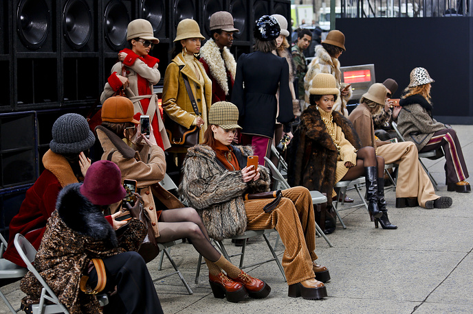 Models wearing fashion from the Marc Jacobs collection are seated after walking a sidewalk runway on Park Avenue during New York Fashion Week, USA, February 16
