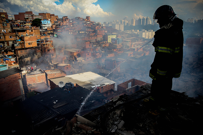 A Brazilian firefighter works at the scene of a fire in Paraisopolis, the second biggest slum of Sao Paulo, Brazil, March 1