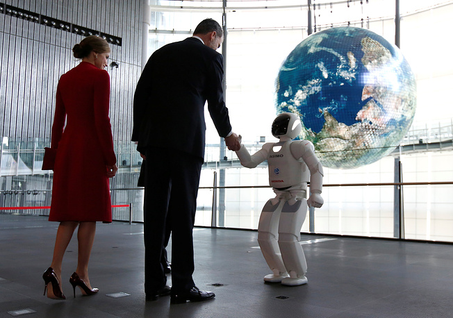 Spain's King Felipe, accompanied by Queen Letizia, shakes hands with Honda Motor's humanoid robot Asimo as they visit Miraikan (National Museum of Emerging Science and Innovation) in Tokyo, Japan, April 5