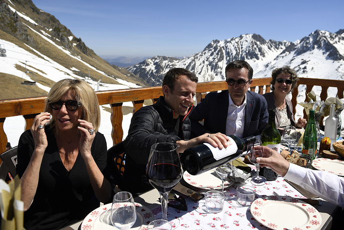 Emmanuel and Brigitte Macron sit on a chairlift on their way to the mountain top for a lunch break during a campaign visit in Bagneres de Bigorre, 2017