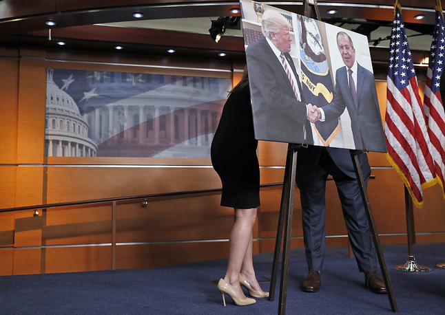 An aide speaks with US lawmaker Joe Crowley on Capitol Hill in Washington behind a photograph of President Donald Trump and Russian Foreign Minister Sergey Lavrov, USA, May 17