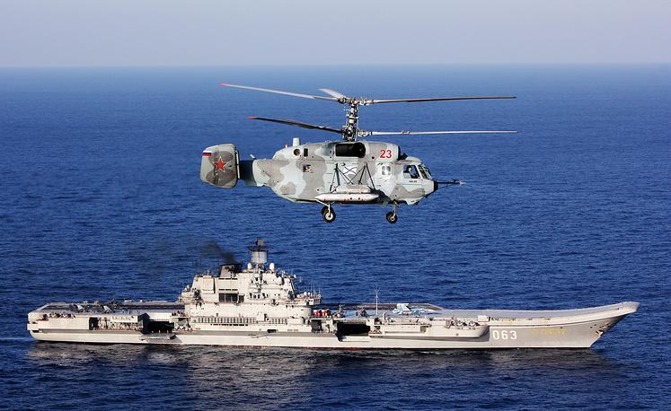 Kamov Ka 52 helicopter over Admiral Kuznetsov aircraft carrier