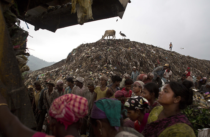 Indian ragpickers wait to collect recyclable materials as a truck prepares to unload garbage at a garbage dumping site on the outskirts of Gauhati, Assam state, India, June 5