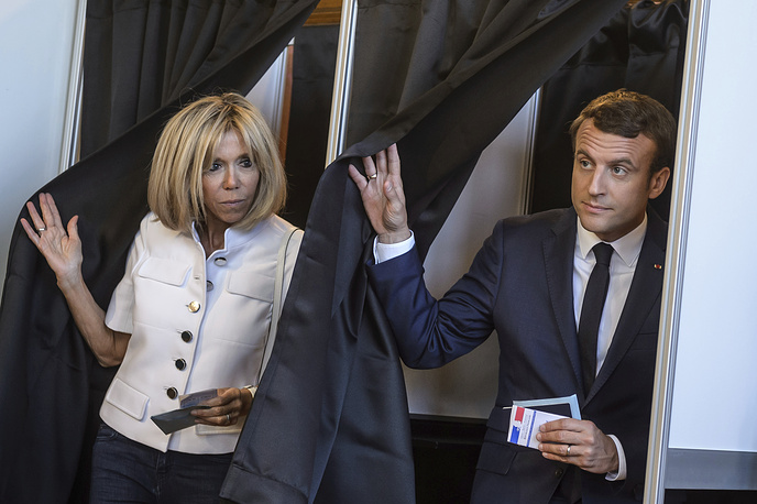 French President Emmanuel Macron and his wife Brigitte Macron leave a polling booth as they vote in the first round of the two-stage legislative elections, in Le Touquet, France, June 11