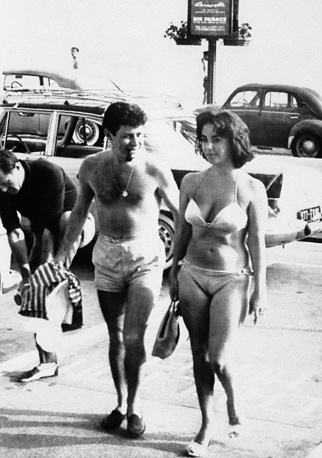 Singer Eddie Fisher and actress Elizabeth Taylor wearing bikini as they walk on Croisette Boulevard, 1959, Cannes, France