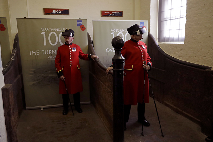 Chelsea pensioners pose for photographers by wearing virtual reality headsets during an exhibition launch inside 18th century vaulted stables at the Household Cavalry Museum in London, July 25