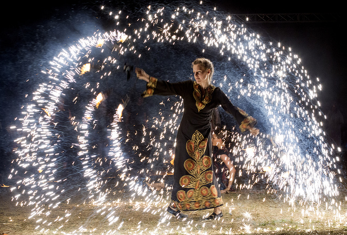 A woman performs a fire show at the Cucuteni International festival near Ivancea village, Moldova, July 22