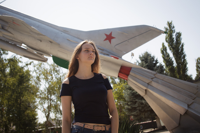 For the first time in Russia's modern history, girls will be admitted to the Krasnodar High military aviation school for pilots this year. Photo: A girl who applied for admission to the Krasnodar High military aviation school for pilots named after Anatoly Serov, stands next to a monument to the MiG-21f-13 aircraft