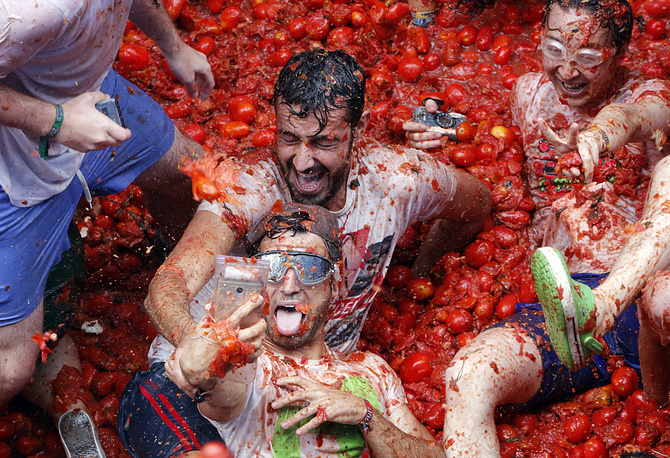 "Revelers take pictures as they enjoy throwing tomatoes at each other, during the annual ""Tomatina"", tomato fight fiesta, in the village of Bunol, Spain, August 30"