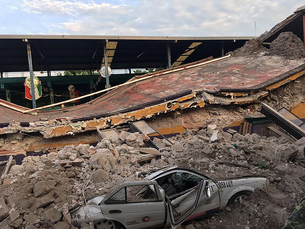 A car sits crushed, engulfed in a pile of rubble from a building felled by a 7.1 earthquake, in Jojutla, Morelos state, Mexico