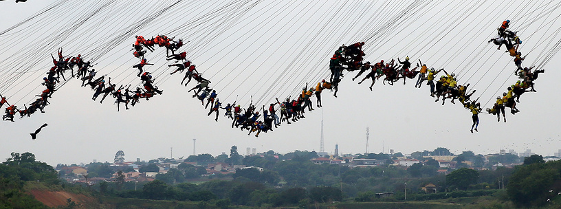 """Daredevils jump off a 30-meter high bridge, in Hortolandia, Brazil, on October 22.  According to the organizers, 245 people were attempting set a new world record for """"rope jumping"""", in which people, tied to a safety cord, jump off a bridge"""