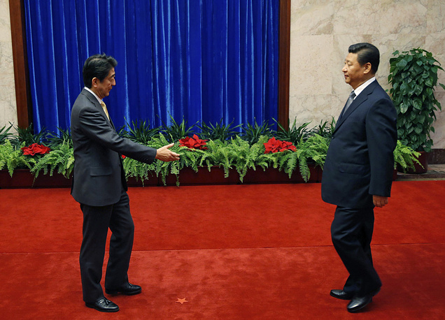 Japan's Prime Minister Shinzo Abe and China's President Xi Jinping, prepare to shake hands during their meeting at the Great Hall of the People in Beijing, 2014. The handshake between Xi and Abe marked the first meeting between the two men since either took power, and a first gesture toward easing two years of high tensions