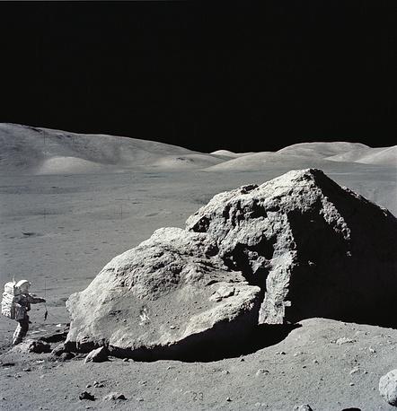 Astronaut Harrison H. Schmitt is photographed standing next to a huge, split boulder at the Taurus-Littrow landing site on the moon