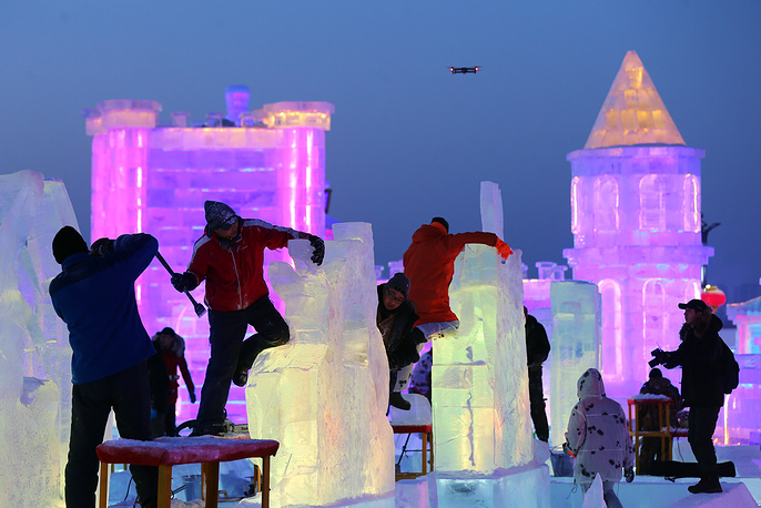 Participants carve their ice sculptures during the ice sculpture competition