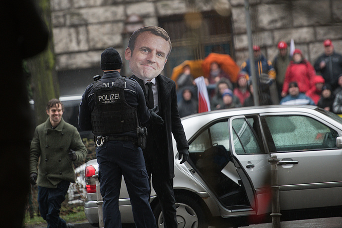 An activist of Avaaz civic organization wears a mask of French President Emmanuel Macron at the headquarters of the German Social Democrats  in Berlin, Germany, January 11