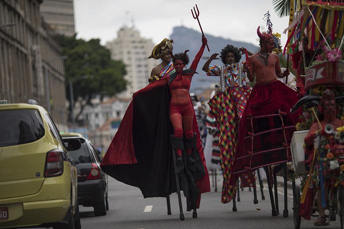 """Revelers perform on stilts during the """"Escravos da Maua"""" block party in Rio de Janeiro"""