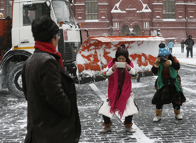 Tourists taking snapshots in snow-blanketed Red Square, Moscow, Russia, February 4