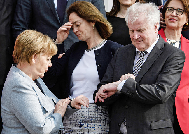 German Chancellor Angela Merkel and German Interior Minister Horst Seehofer look on their watches as German Justice Minister Katarina Barley gestues after a group shot during a cabinet meeting at the Meseberg palace in Gransee, Germany, April 10