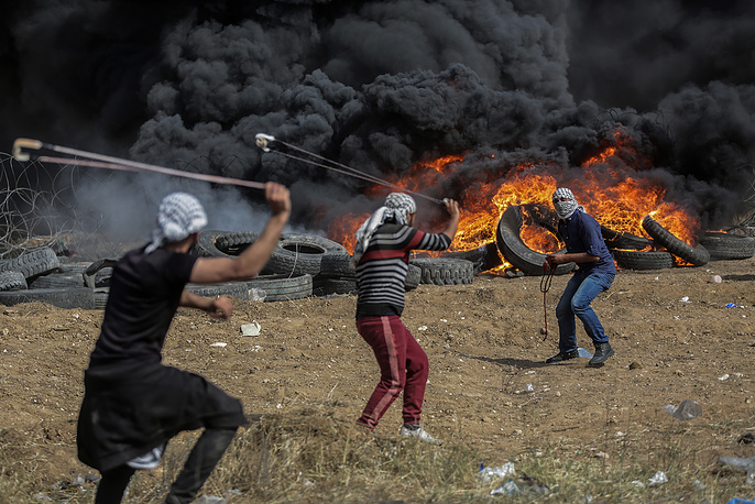 Palestinians protesters throw stones during clashes after protests near the border with Israel, in eastern Gaza City, April 27