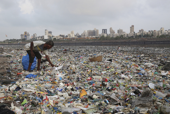 A man collects plastic and other recyclable material from the shores of the Arabian Sea, littered with plastic bags and other garbage, in Mumbai, India