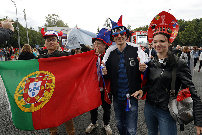 Fans hold the Portuguese national flag as they attend the opening of the FIFA Fan Fest on Vorobyovy Gory (Sparrow Hills)