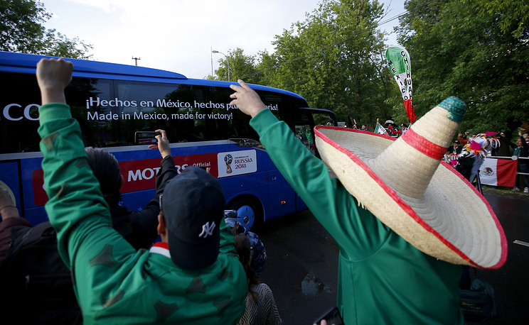 A Mexico fan wearing a tradition Mexican hat, cheers as his team, the Mexico national soccer team, boards a bus after training session at the 2018 soccer World Cup, in Moscow