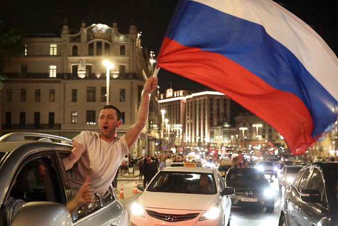 Russian football fan waves national flag in central Moscow