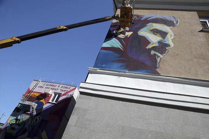 Russian graffiti artists of the SuperNovaNet team making a mural of Argentina's Lionel Messi