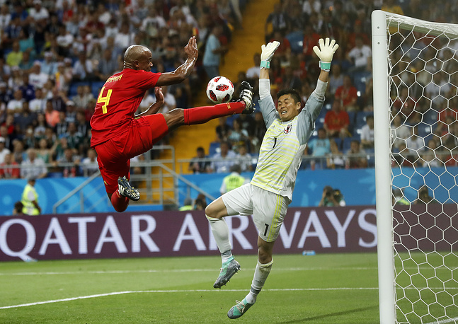 Belgium's Vincent Kompany jumps for the ball in front of Japan goalkeeper Eiji Kawashima during the round of 16 match between Belgium and Japan in the Rostov Arena, in Rostov-on-Don, July 2