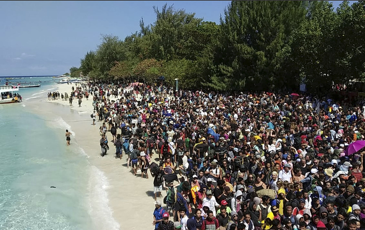 Tourists affected by a strong earthquake line up on a beach as they wait to be evacuated on Gili Trawangan Island, Indonesia