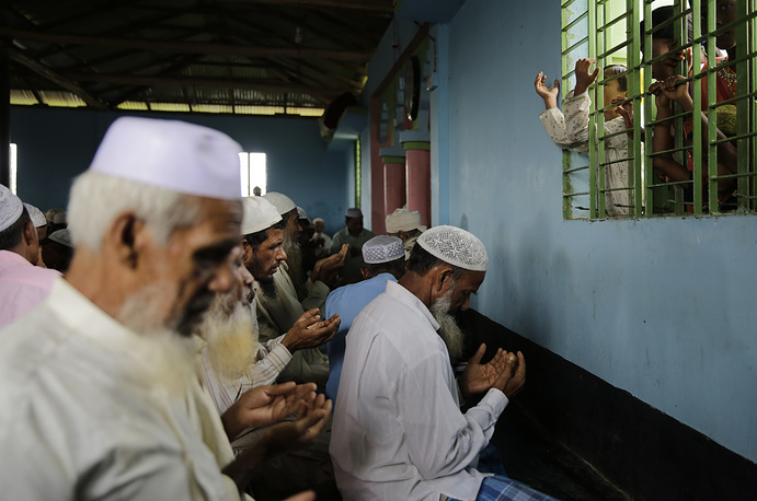 Children of Rohingya refugees watch from a window as elders pray inside a mosque on Eid al Adha at Kutupalong refugee camp, Bangladesh