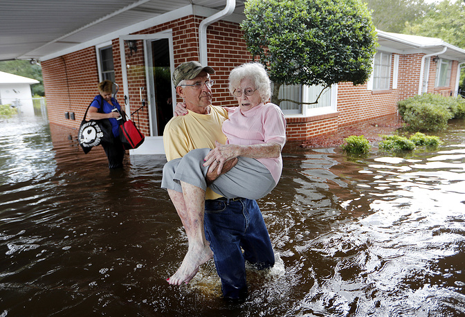 People leave their flooded home in Spring Lake, North Carolina