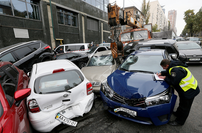 A police officer works at the site of a road traffic accident after a mobile crane crashed into passenger vehicles in Kiev, October 23