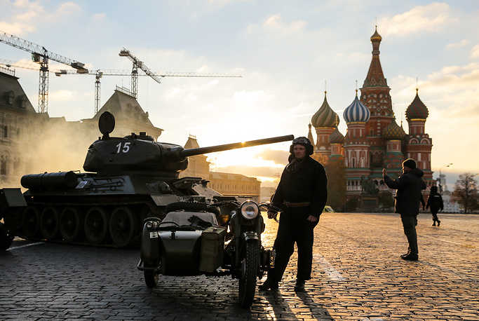 A participant dressed as a Red Army soldier stands next to a motorcycle with a sidecar and a tank during the dress rehearsal of a historical re-enactment, which marks the 77th anniversary of the 1941 military parade in Red Square, Moscow, November 5