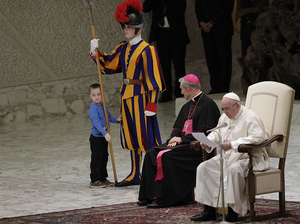 A child stands by a Swiss guard after making his way to the area where Pope Francis and Archbishop George Gaenswein are sitting, during the pontiff weekly general audience in the Paul VI Hall at the Vatican, November 28. Pope Francis praised the freedom, albeit undisciplined, of a hearing impaired child who climbed onto the stage during his general audience to play