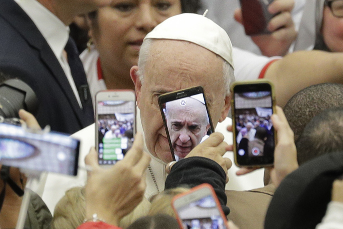 Pope Francis is framed by cellphones as he arrives for his weekly general audience, in the Pope Paul VI hall, at the Vatican, January 9