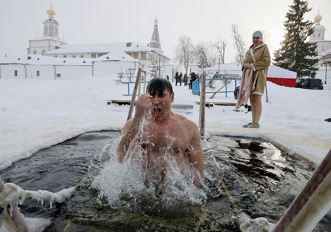 A Russian Orthodox believer crosses himself as he bathes in an ice hole during a traditional Epiphany celebration in a lake near Valdai-Iverskiy Monastery, Novgorod region, January 19
