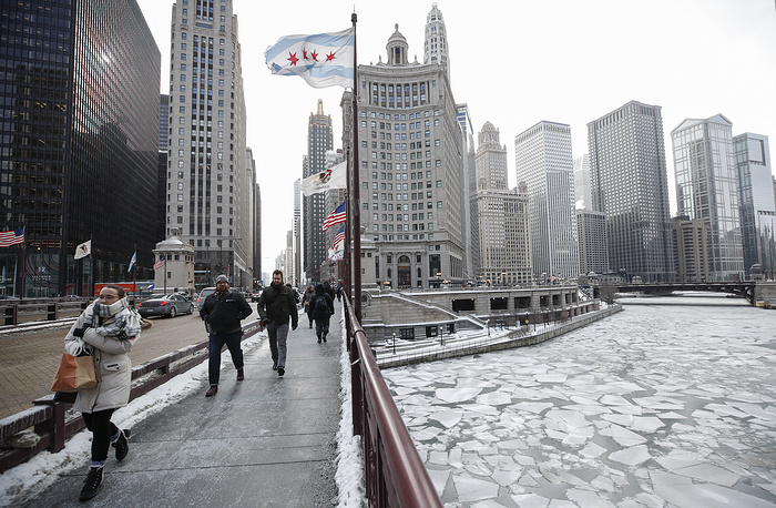 Pedestrians walk along Michigan Avenue above the frozen Chicago River in Chicago