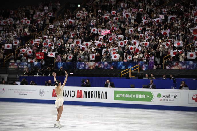 Satoko Miyahara of Japan cheered by the spectators with national flags after performing in the ladies short program at Saitama Super Arena
