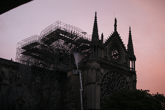 The Notre Dame Cathedral as seen at sunrise while firefighters put out remaining pockets of the blaze, Paris