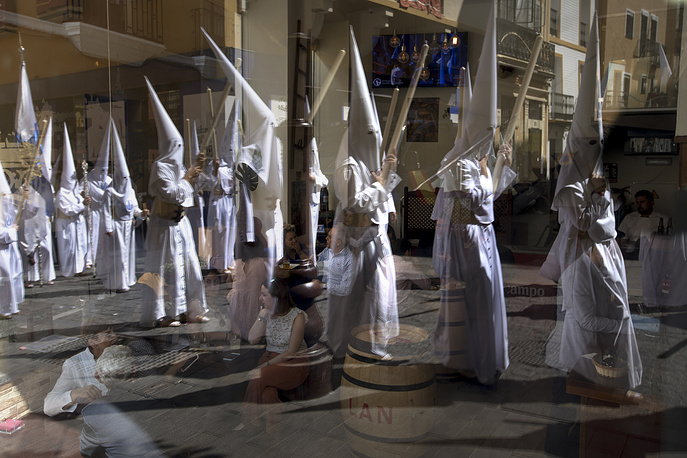 "Hooded penitents from ""La Candelaria"" brotherhood are seen reflected in a restaurant window as they take part in a procession in Seville"