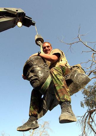 Английский военный на фрагменте памятника Саддаму Хусейну, 1 апреля 2003