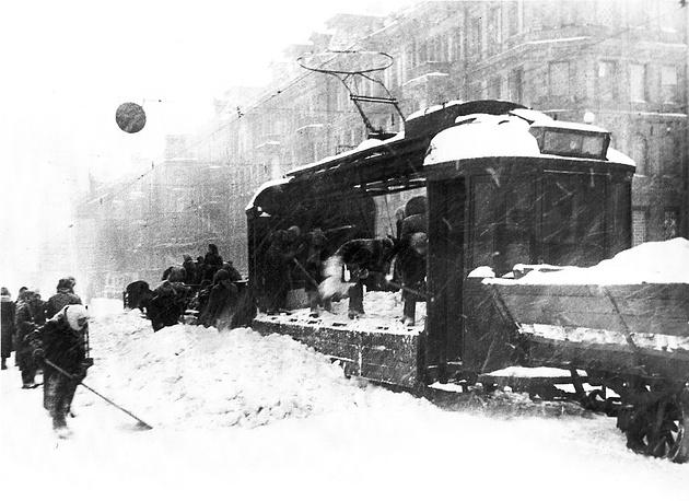 Погрузка сколотого льда и снега в грузовой трамвай на проспекте 25-го октября (Невский проспект) в блокадном Ленинграде. 1943 г.